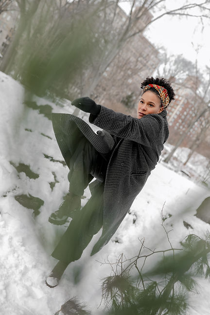 Destini Rogers, a short haired black woman dances outside in the snow. She wears a checkered coat and a headband in her hair. We see her standing on one leg with pine needles in the foreground.