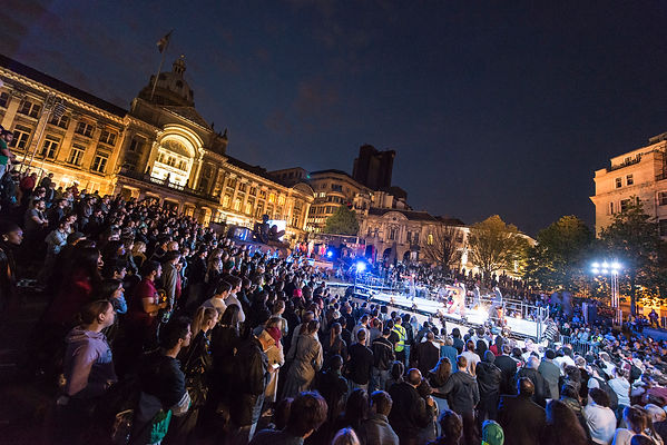 A large crowd gathers in a city square in front of a gothic building to watch a performance.