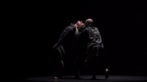 One dancer catches another's head on a black stage at Detroit City Dance Festival