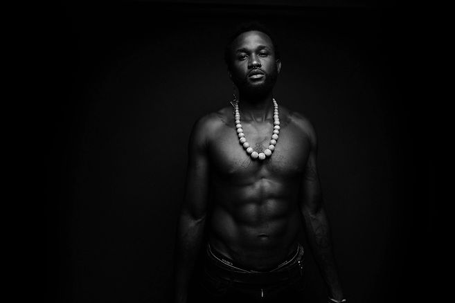 Tyresse Bracy, a black man with a septum piercing and short hair, poses shirtless in front of an all black background. The photograph is black and white. He wears light color beads around his neck.
