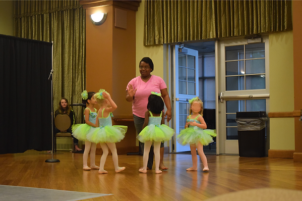 Abra Myles, a dark skinned woman with short hair, give a high five to one of her four young students in tutus in a green room with wooden floors and curtains.