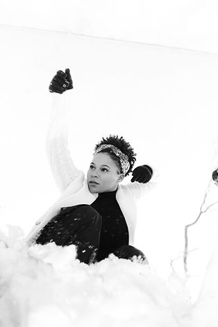 Destini Rogers, a short haired black woman dances in the snow with her hand over her head, a headband on her head, and a serious look on her face.