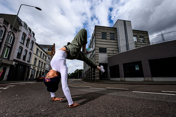 """Logan """"Logistix"""" Edra breakdances in the street. She is balanced on her hands with her feet in the air behind her head."""