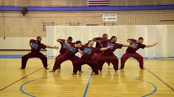 Dancers post together in a group in a gymnasium. They are all reaching to their left and looking at their hands. They all wear maroon sweatsuits.