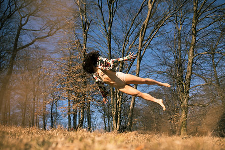 Maartje jumps in the are in the woods. Her face is obscured by her hair and she is parallel to the ground.