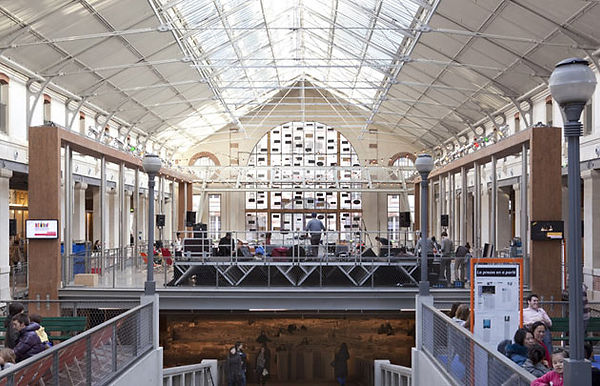 An interior view of Le Centrequartre in Paris. People sit at tables on balconies with large windows in the background and skylights above.