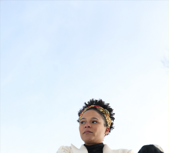 Destini Rogers, a black woman with short hair and a colorful headband, looks off to the side with nothing but the clear blue sky behind her.