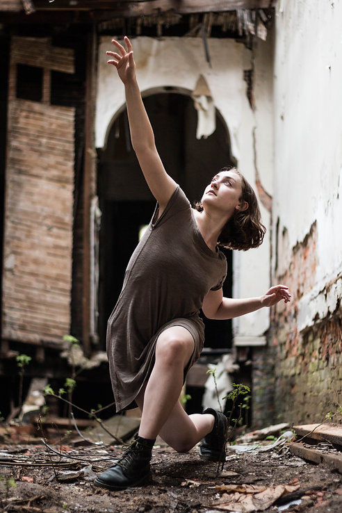 Hallie Chametzky dances in a crumblign building, reaching towards the sky in a deep lunge.