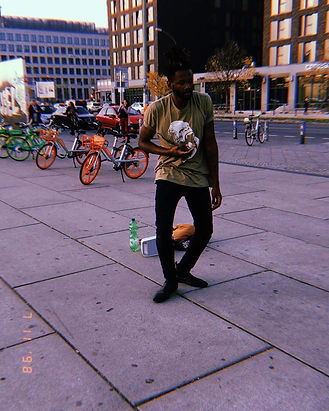 Tyresse Bracy, a black man with short hair, dances on a concrete sidewalk in a city with a green shirt and black jeans on. There are bicycles parked in the background and speaker behind him.