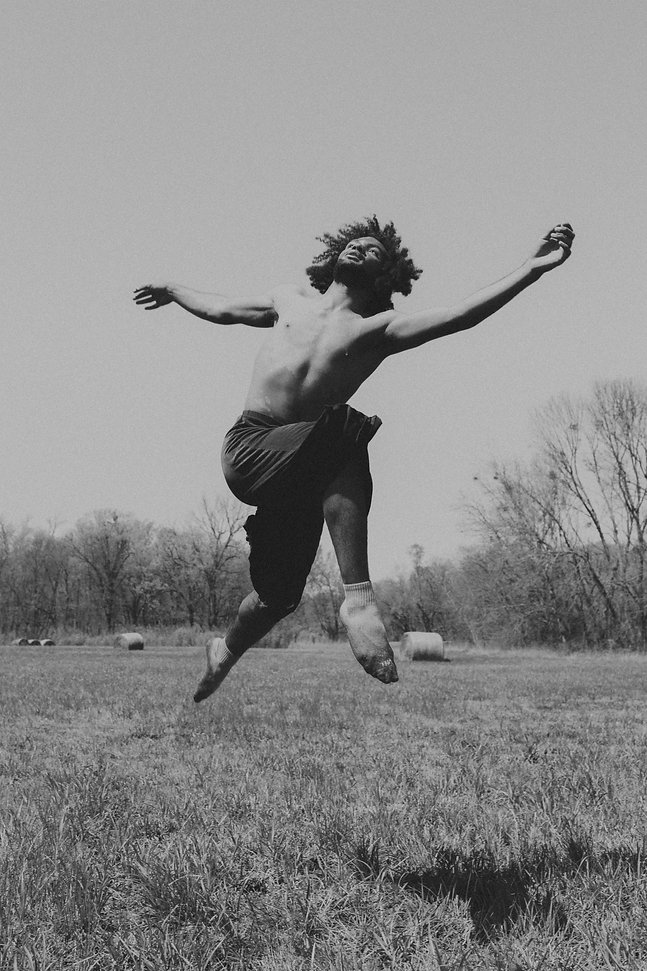 A black and white photo of Gabe Flowers leaping in the air in a field.