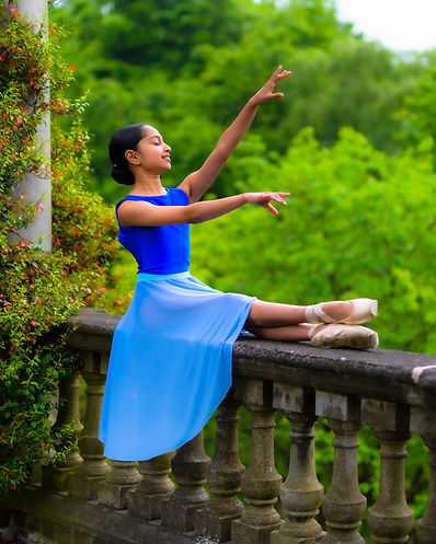 Aarya Shenoy poses in ballet attire and pointe shoes on an old ledge in front of greenery. She has dark skin and hair, which is slicked into a low bun. Her eyes are closed.