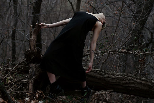 A white woman in a black dress is in the woods, holding onto a fallen tree and leaning backwards. Her face is unseen behind her shoulders.