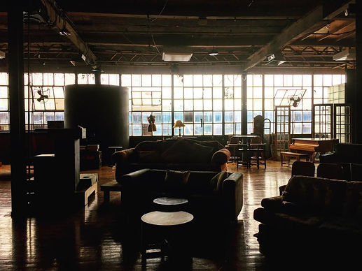 An interior view of The Space Upstairs in Pittsburgh, PA. We see lots of different furniture in a warehouse-like setting with a full wall of windows in the background.