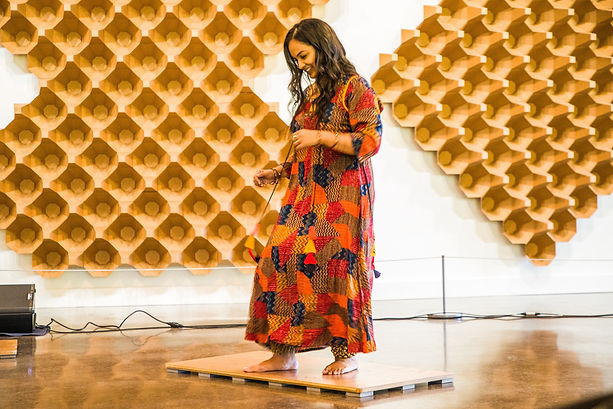 Brinda Guha smiles while performing a dance wearing a multicolored, patchwork dress in a room with soundproofing materials on the walls