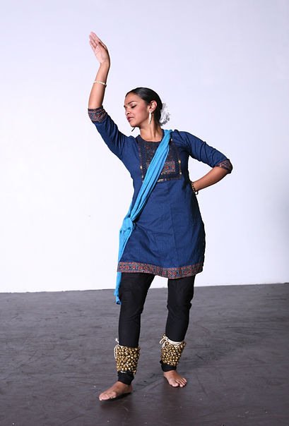 Brinda Guha poses mid dance in a blue tunic on a black floor with a white background.
