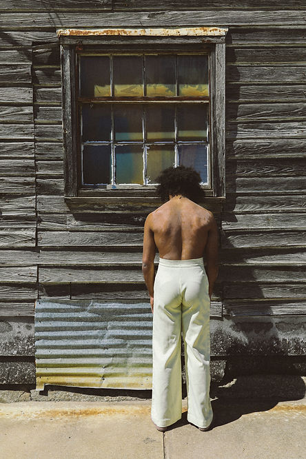 Gabe Flowers, shirtless in high-waisted yellow pants, leans his head against an old wooden windowsill. We see just his back and the wooden wall in front of him.