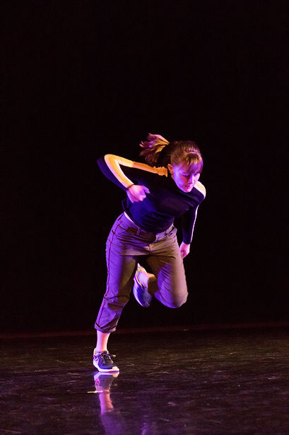 Lindsey Jennings dances in an all black space in sneakers, pants and a shirt.