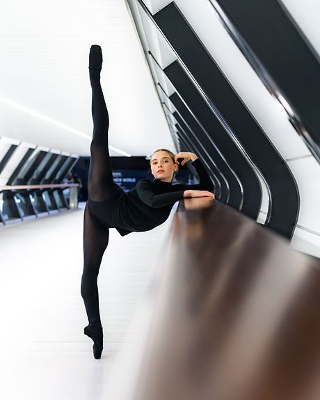 Hannah Martin poses in a penché in a long hallway. She is leaning on the railing and looking directly at the camera. She has light skin and dark hair and wears all black including pointe shoes.