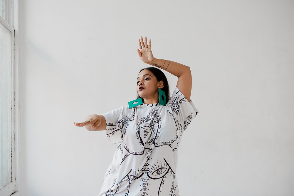 Brinda Guha dances in a white room in a white LVDF shirt and large turquoise earrings.