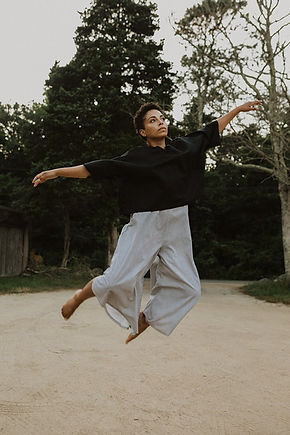 Hannah Hodson looks skyward in grey pants and a black shirt while seemingly floating in midair infront of trees.