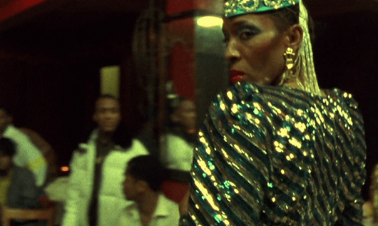 A black woman in a sequined gold and green outfit looks over her shoulder toward the camera.