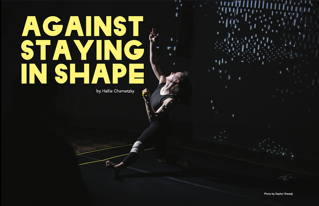 """Hallie Chametzky dances in all black in an all black space with an image projected on her body. She reaches towards the ceiling. The overlaid text reads """"Against Staying in Shape"""" by Hallie CHametzky. Photo by Zephyr Sheedy."""