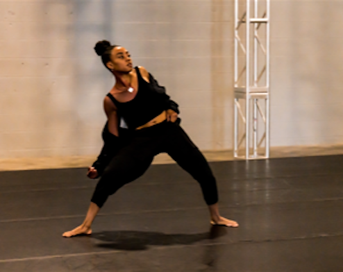 Marcella Lewis dances in all black on black marley with a white wall behind her.