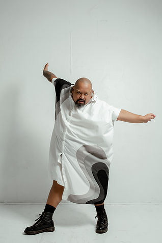 Mike Esperanza dances with arms splayed in combat boots and a long white tunic. He stares directly at the camera.