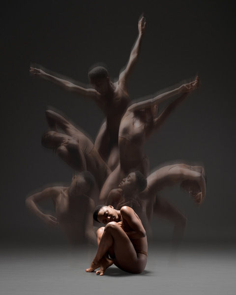 Joy Marie Thompson sits in the foregrround naked while ghostly images of herself dancing spring from her back.