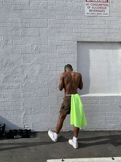 Byron Tittle moves towards a white wall facing away from the camera. He has a lime green shirt tucked into the wait of his shorts and is looking down.