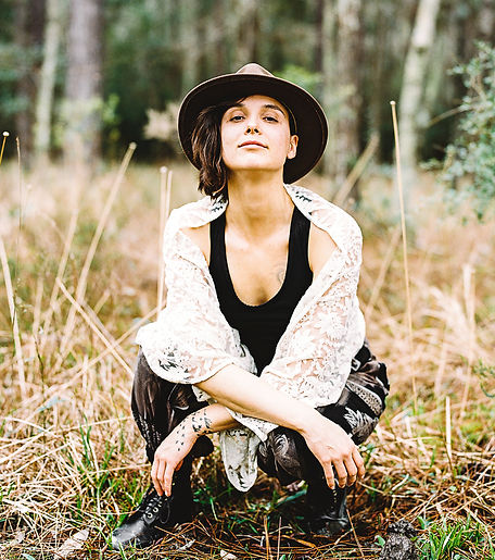 Maygen Nicholson squats in a field of tall grass. They have a wide brim hat, lace shirt, black tank top, black boots, and black pattern print pants on.