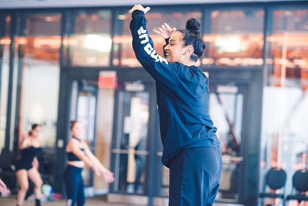 Brinda Guha leads class at Wind Up Dance Tour in Bethlehem in 2019 wearing all black with her arms above her head and a smile on her face.