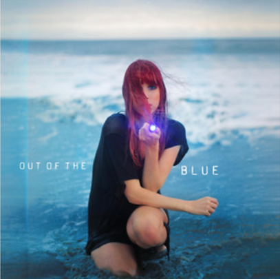 "Juliette Irons crouches in the ocean pointing a flashlight at the camera on the cover of here EP ""Out of the Blue"""
