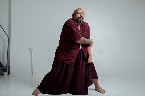 Mike Esperanza poses in a white room in a maroon shirt and maroon floor-length skirt. He stands with his legs wide, holding his left elbow and staring right at the camera.