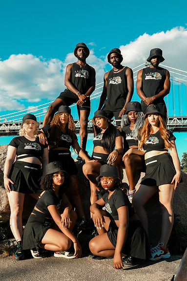 The dancers of Afro Afriqué pose in a group in matching black outfits with black bucket hats looking straight at the camera.