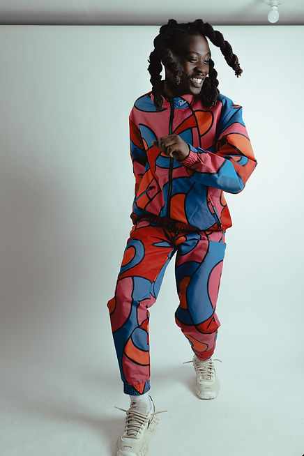 Treyveon Anderson wears a multicolor track suit in an all room, smiling while he dances.