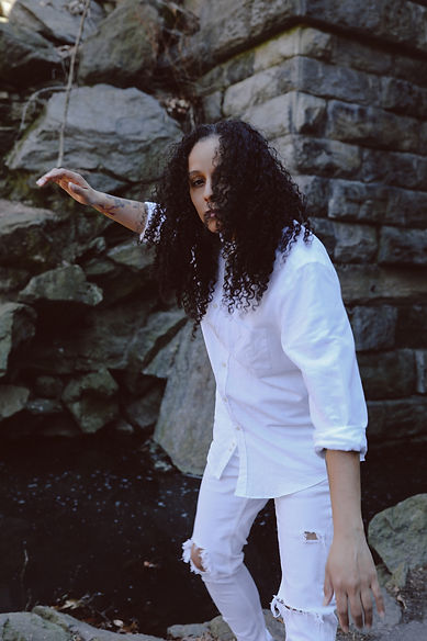 Dolores Sanchez poses in front of rocks and a cobblestone wall in all white.