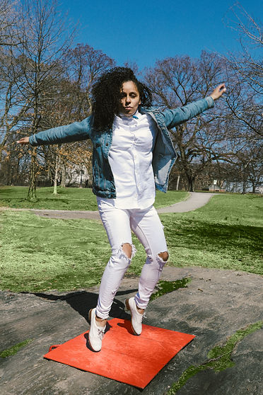 Dolores Sanchez dances on a red tap board outside in an all white outfit and jean jacket.