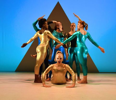 Dancers of Rosie Kaye Dance Company pose in shiny unitards of gold and teal. They are in two-dimensional, angular poses. Behind them is a large triangle.