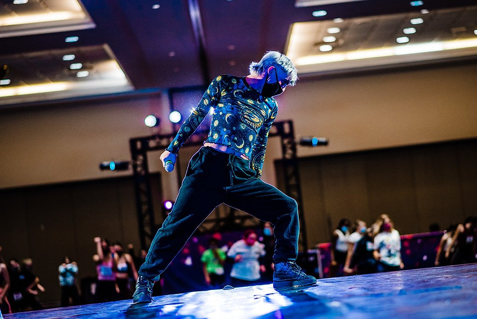 Zack Venegas leads a class at a dance convention. His hair is blue and he wears a tight shirt with stars, moons, and galaxies on it. He stands in a lunge to the left looking over his left leg with commanding power.