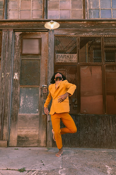 Gabe Flowers stands in turned out passe looking up to the sky wearing an orange suit. He is in front of an all wooden building.