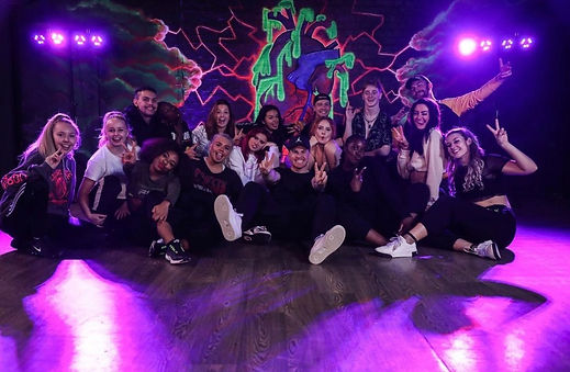 A group of dancers pose in a dance studio in front of a graffiti mural.