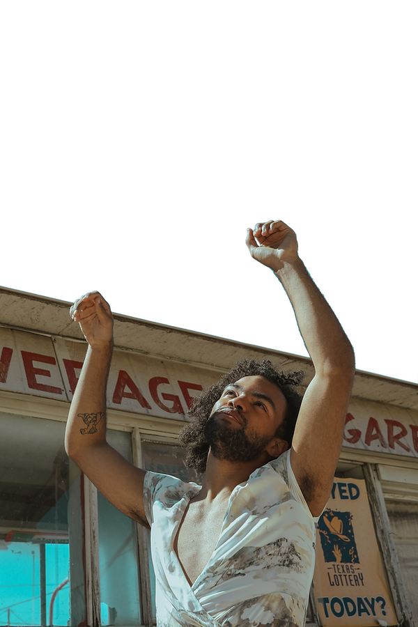Gabe Flowers looks and reaches into a blue sky in front of an old building while he wears a flowy top.