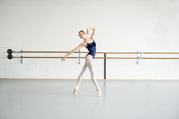 Leonie de Ripaisel poses in an all white ballet studio in a leotard and tights. She has light skin and blonde hair and wears a blue leotard and pink tights. She stands en pointe in ballet fourth position.