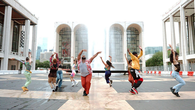 A group of dancers dancing outside the fountain at Lincoln Center. They are spread out and walking in different directions with their arms above their heads.