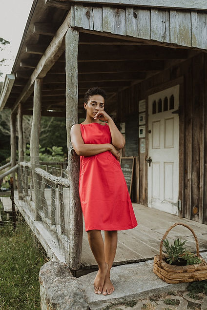 Hannah Hodson leans on a wooden pole on a rustic wooden porch. She is barefoot in a red dress and looks directly at the camera.