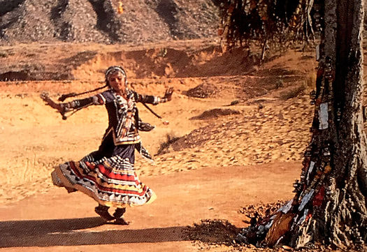 An indian woman dances near a tree in a traditional outfit in a desert-like setting