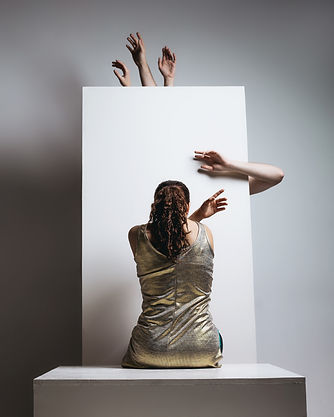 Jordyn Santiago sits in a gold dress with her back to the camera. She is reaching her hand to the right while a bunch of other hands and arms reach around a white block in front of her.