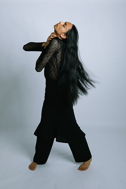 Christian Saludez, a filipino man with long dark hair. Grabs his neck and looks to the sky in front of a grey background. He wears a black lace shirt and black pants.