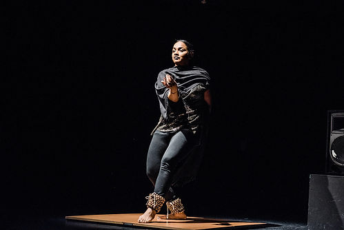 Brinda Guha performs a kathak dance in all black in a spotlight with a black background.